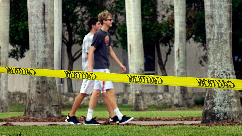 Students walking behind caution tape