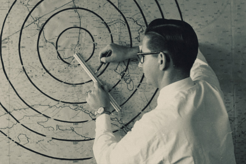 student plots points on large map in radar laboratory