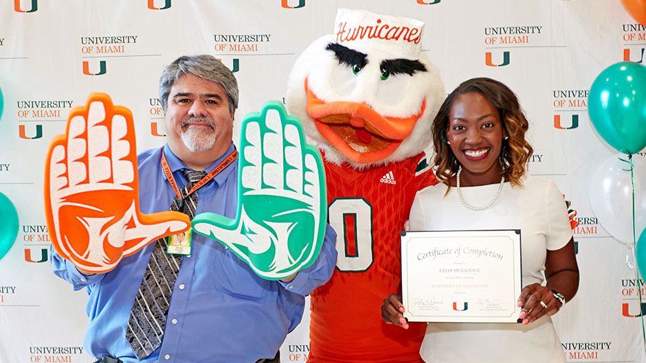 Isamel Pimienta and Celia McFadden pose with Sebastian the Ibis at the Essentials of Leadership graduation celebration