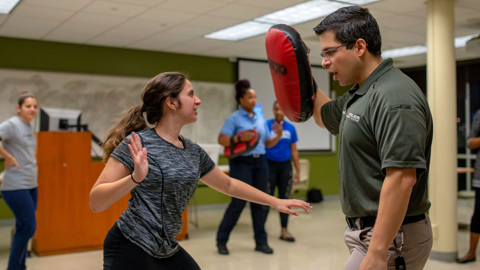 Student with UMPD instructor in SAFE self-defense class