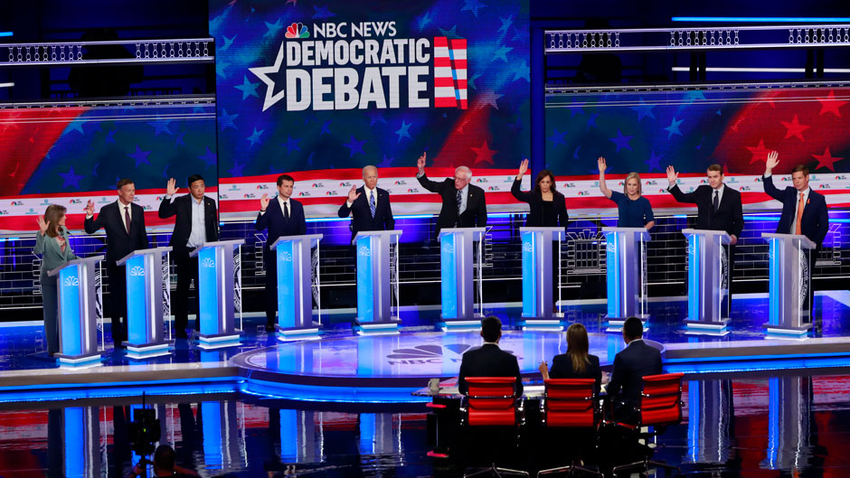 Democratic presidential candidates, author Marianne Williamson, former Colorado Gov. John Hickenlooper, entrepreneur Andrew Yang, South Bend Mayor Pete Buttigieg, former Vice President Joe Biden, Sen. Bernie Sanders, I-Vt., Sen. Kamala Harris, D-Calif., Sen. Kirsten Gillibrand, D-N.Y., former Colorado Sen. Michael Bennet, and Rep. Eric Swalwell, D-Calif., raise their hands when asked if they would provide healthcare for undocumented immigrants, during the Democratic primary debate hosted by NBC News at the Adrienne Arsht Center for the Performing Arts, Thursday, June 27, 2019, in Miami. (AP Photo/Wilfredo Lee)