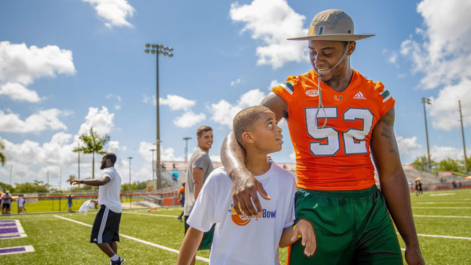 Hurricanes football lineback Patrick Joyner, Jr. with a participant of the program's free youth football camp at Harris Field Park.