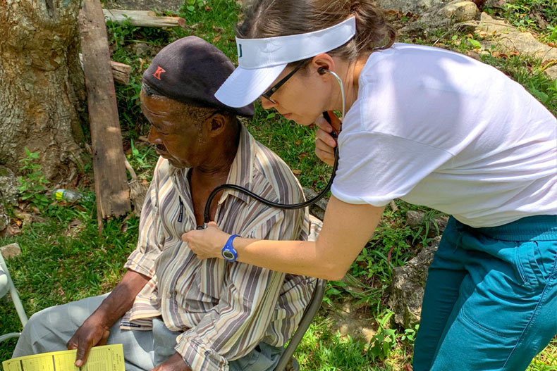 Nursing student Andrea Leiner examines a patient in Jamaica