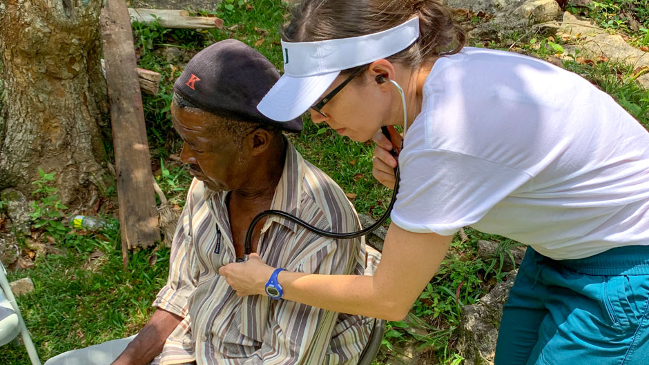 Nursing student Andrea Leiner examines a patient in Jamaica