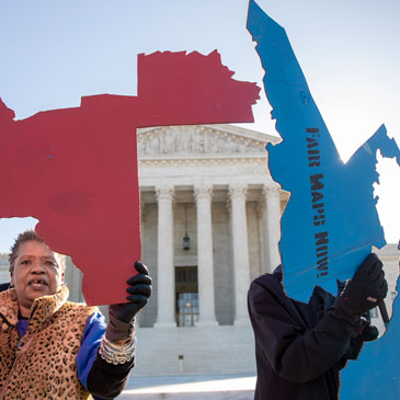 Activists at the Supreme Court opposed to partisan gerrymandering hold up representations of congressional districts from North Carolina, left, and Maryland, right. Photo: Carolyn Kaster/Associated Press