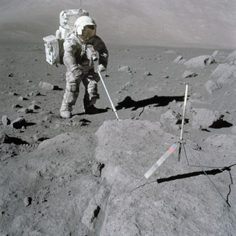 Scientist-astronaut and lunar module pilot Harrison Schmitt uses an adjustable sampling scoop to retrieve lunar soil samples during the Apollo 17 moon mission of 1972, the final mission of NASA's Apollo program.