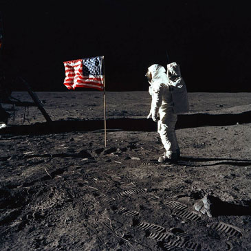 Astronaut Edwin E. Aldrin Jr., lunar module pilot of the first lunar landing mission, poses for a photograph beside the deployed United States flag during an Apollo 11 extravehicular activity (EVA) on the lunar surface.