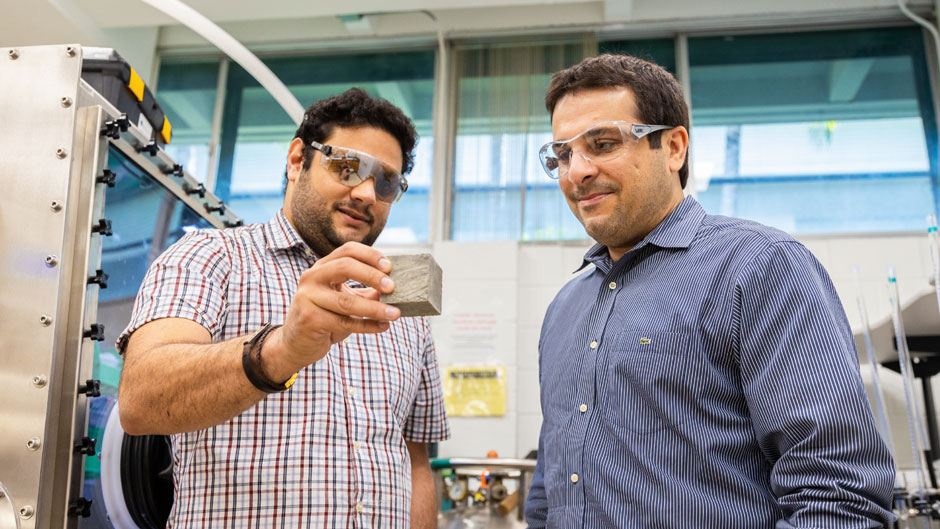 Engineering researcher Ali Ghahremaninezhad (right) is testing different biopolymers to determine which would be most effective in turning lunar soil into a hardened, concrete-type substance.