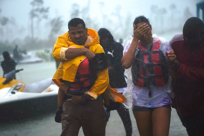 A family is escorted to a safe zone after they were rescued as Hurricane Dorian continues to rain in Freeport, Bahamas, Tuesday, Sept. 3, 2019. The center of Hurricane Dorian is finally moving away from Grand Bahama island but the U.S. National Hurricane Center says the island will continue getting dangerous winds and life-threatening storm surge through the evening. (AP Photo/Ramon Espinosa)