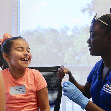 Nichelle Decius, a member of the UM-NSU CARD research staff, takes a saliva sample from a girl who is enrolling in the SPARK study.