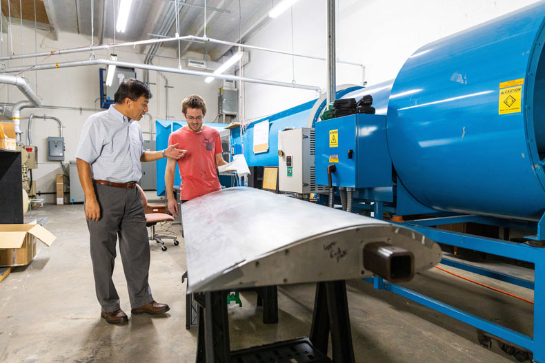 Professor GeCheng Zha and College of Engineering graduate student Brendan McBreen examine a prototype wing containing micro-compressors that would generate vertical lift and propulsion in an electric V/STOL aircraft.