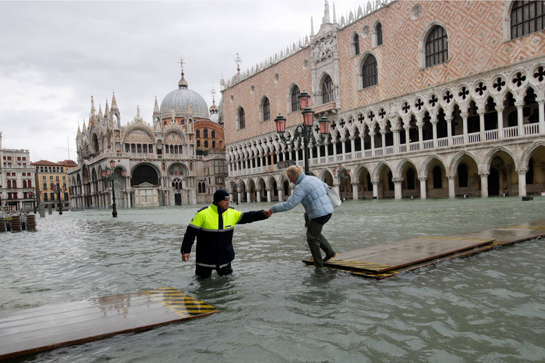 A city worker helps a woman who decided to cross St. Mark square on a gangway, in spite of prohibition, in Venice, Italy, Sunday, Nov. 17, 2019. Venetians are bracing for the prospect of another exceptional tide in a season that is setting new records. Officials are forecasting a 1.6 meter (5 feet, 2 inches) surge Sunday. That comes after Tuesday's 1.87 meter flood, the worst in 53 years, followed by high tide of 1.54 meters on Friday. (AP Photo/Luca Bruno)