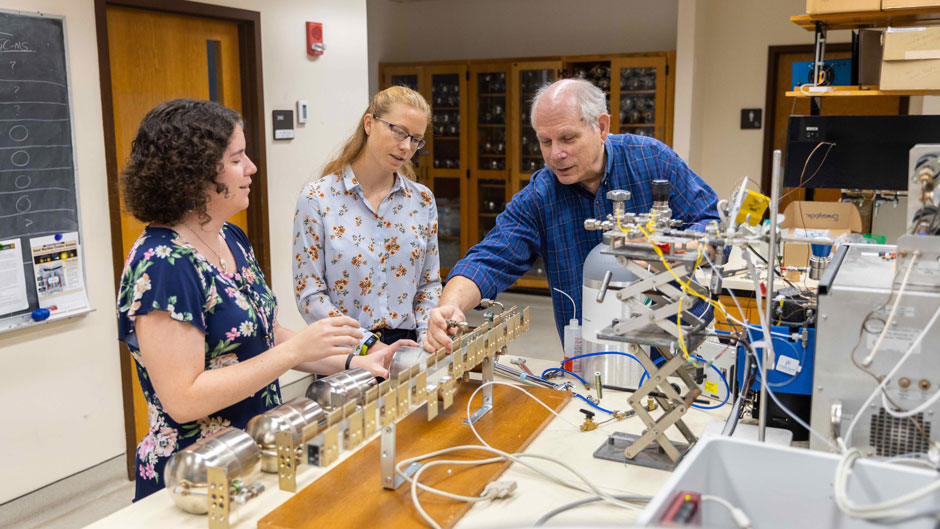 Atmospheric scientist Elliott Atlas and postdoctoral students Katie Smith, left, and Victoria Treadway examine some of the instruments that are used to collect and analyze air samples from the upper stratosphere.