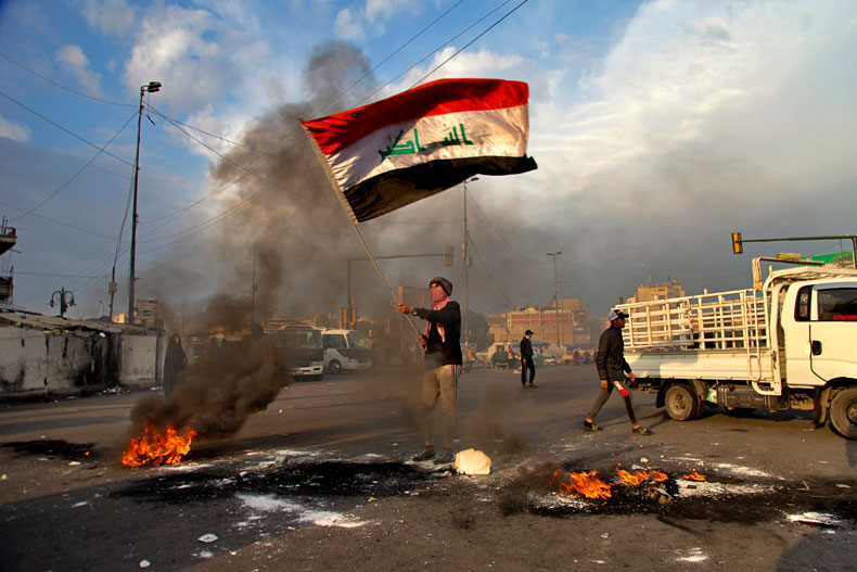 A protester waves the Iraq flag while demonstrators set fire to close streets near Tahrir Square during a demonstration to protest against the Iranian missile strike, in Baghdad, Iraq, Wednesday, Jan. 8, 2020. Iran struck back at the United States early Wednesday for killing a top Revolutionary Guard commander, firing a series of ballistic missiles at two military bases in Iraq that house American troops in a major escalation between the two longtime foes. (AP Photo/Khalid Mohammed)