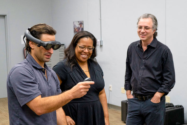 The Center for Computational Science's Michael Mannino demonstrates Magic Leap's headset for the Frost School's Valerie Coleman and Jeffrey Marc Buchman.