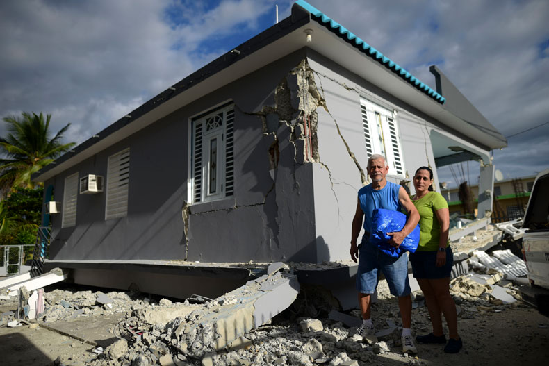 67 year-old William Mercuchi, center, and his daughter Joan pose for photos in front of their house that collapsed after the previous day's magnitude 6.4 earthquake in Yauco, Puerto Rico, Wednesday, Jan. 8, 2020. More than 250,000 Puerto Ricans remained without water on Wednesday and another half a million without power, which also affected telecommunications. (AP Photo/Carlos Giusti)