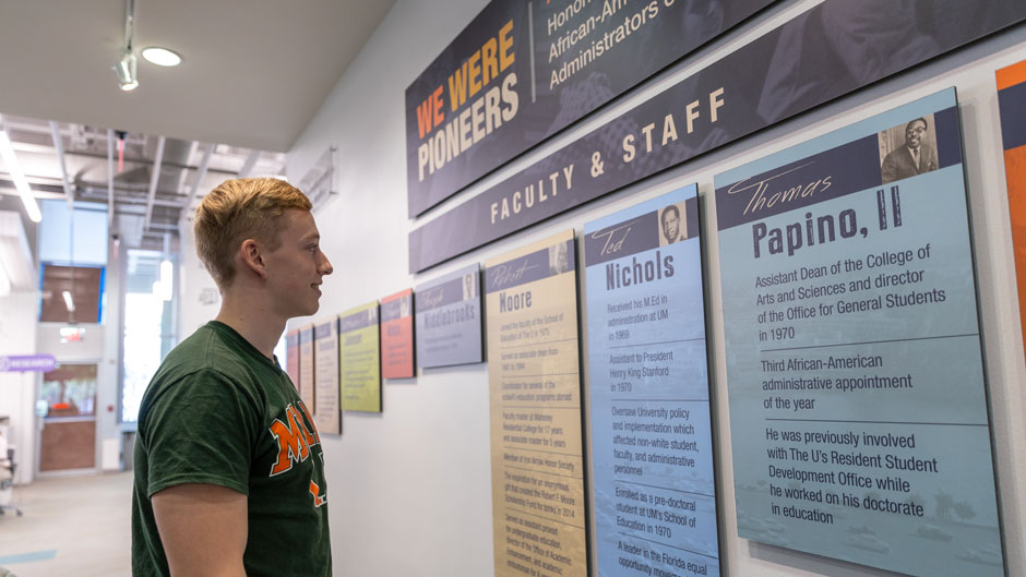 Gabriel Frohlich, a biomedical engineering major, visits the We Were Pioneers exhibit at the Richter Library.