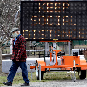 A passer-by wears a mask out of concern for the coronavirus while walking past a public service sign, Tuesday, April 7, 2020, at the Charles River Esplanade park in Boston. Many businesses have closed indefinitely while many people are working from home out of concern for COVID-19. The new coronavirus causes mild or moderate symptoms for most people, but for some, especially older adults and people with existing health problems, it can cause more severe illness or death. (AP Photo/Steven Senne)