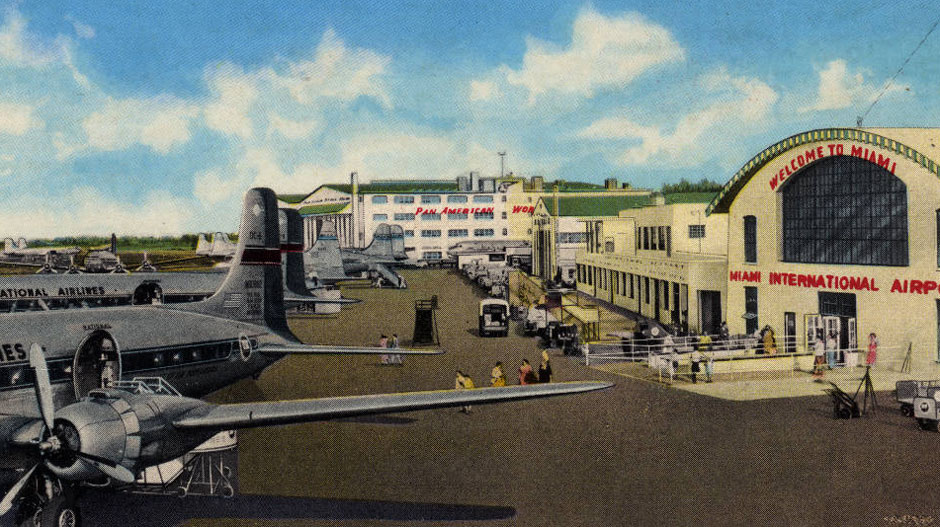 A City of Miami News Bureau photograph of Miami International Airport, showing the Pan American terminal and National Airlines planes. A few travelers walk between the main terminal entrance and the airplanes.