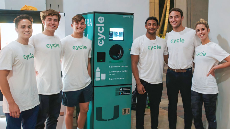 (L-R) Cycle Technology team members Anwar Khan, Connor Pohl, Harrison Mount, Noah Barrows, Colin Hively, and Julie Young (not pictured Jacqueline Dubois and Jack Vandermolen) standing with their reverse-vending machine in the breezeway of the Miami Business School. (Photo Courtesy of Connor Pohl).