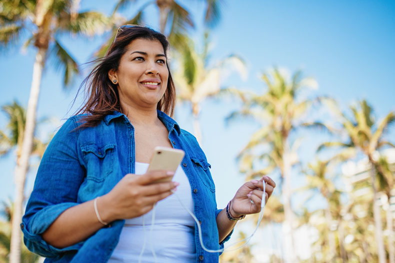 Woman walking and listens to music stock photo