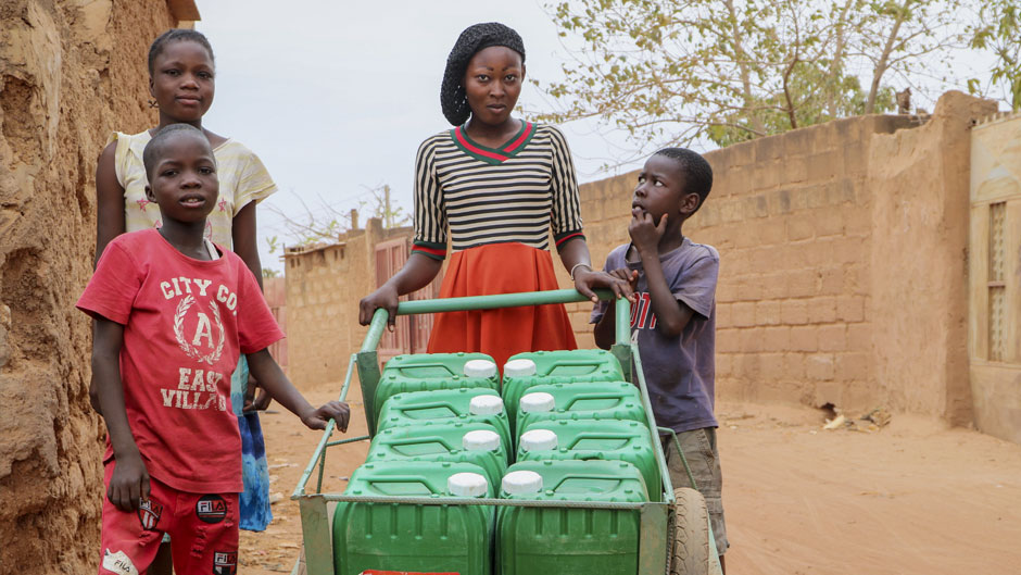 In this photo taken Tuesday, March 24, 2020, a woman pushes a cart of jerry cans of water, as people often have to walk half an hour to the closest water point several times a day and wait in crowded lines in order to get enough water to wash hands, bathe and cook, on the outskirts of Ouagadougou, Burkina Faso. Burkina Faso is one of Africa's nations hardest hit by the coronavirus with one of the highest number of fatalities in sub-Saharan Africa. (AP Photo/Sam Mednick)
