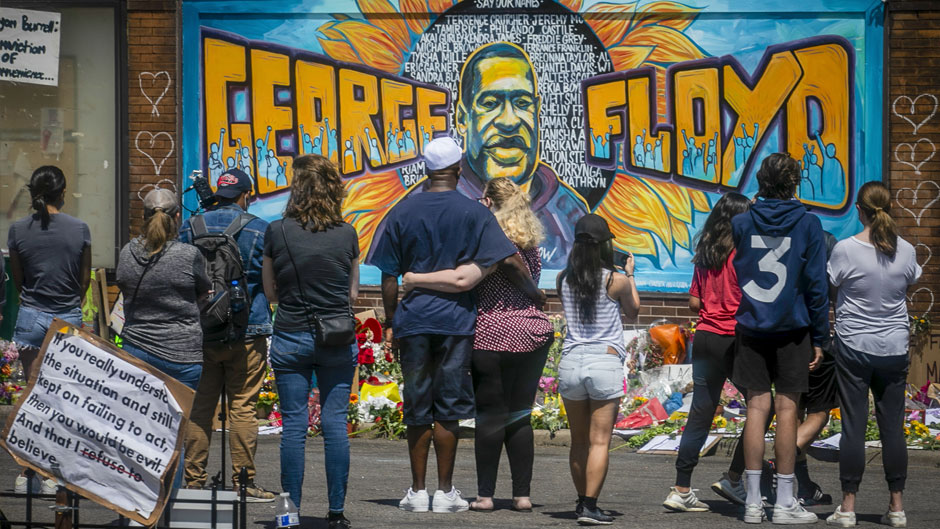 In this May 31, 2020 file photo, visitors make silent visits to organic memorial featuring a mural of George Floyd, near the spot where he died while in police custody, in Minneapolis, Minn. The message from protesters around the United States is that George Floyd is the latest addition to a grim roster of African Americans to be killed by police. (AP Photo/Bebeto Matthews, File)