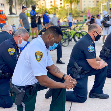 Police officers kneel during a protest in Coral Gables on Saturday, May 30, 2020. Photo courtesy Roy Ramos/WPLG
