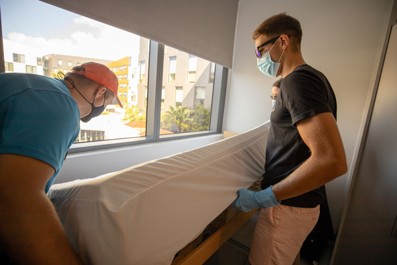 Alexander Miller, a neuroscience major in his second year on campus, puts on sheets with the help of his family as he moves into Lakeside Village on Thursday, August 13, 2020.