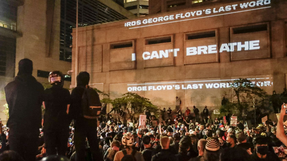 """In this Saturday, July 25, 2020, file photo, the words """"I can't breathe"""" are flashed on a wall during a Black Lives Matter protest in Portland, Ore. Photo: Associated Press"""