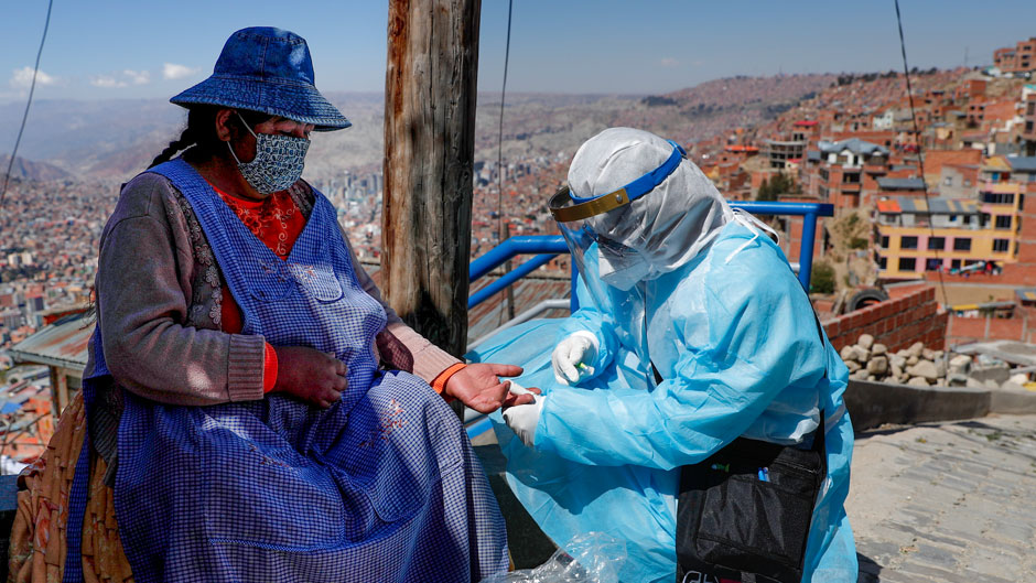 A healthcare worker dressed in full protective gear draws blood from a woman to test for the new coronavirus during a house-to-house COVID-19 testing campaign, in the Villa Rosasani neighborhood of La Paz, Bolivia, Friday, Aug. 28, 2020. (AP Photo/Juan Karita)