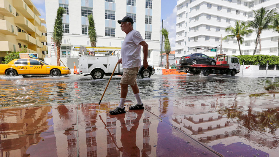 In this Sept. 30, 2015 file photo, Louis Fernandez walks along a flooded street in Miami Beach, Fla. The street flooding was in part caused by high tides due to the lunar cycle, according to the National Weather Service. When Democratic presidential candidates meet in Miami for their first debate it'll be in what you could call the country's Ground Zero for any climate-related sea level rise. (AP Photo/Lynne Sladky, File)