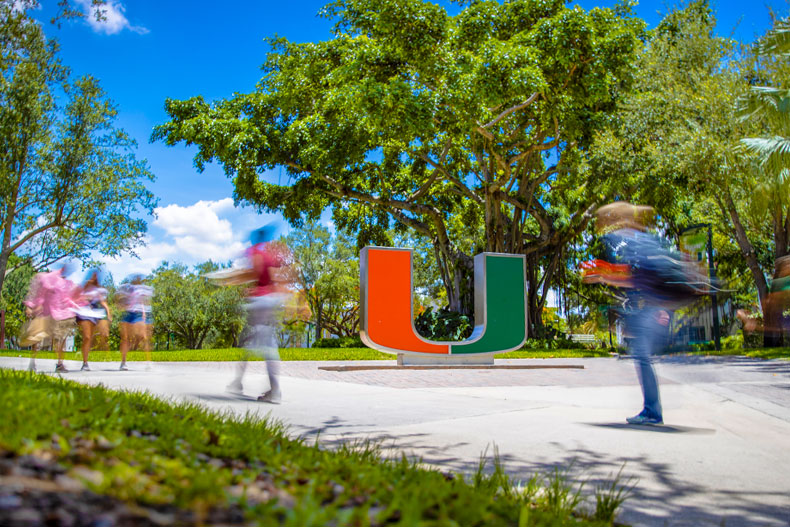 Students walk past the U statue in a blur.