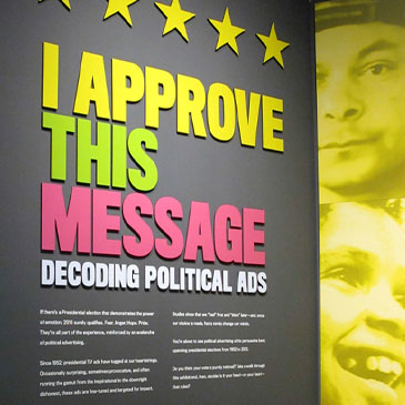 In this July 28, 2016 photo, a sign explains an exhibit on political campaign ads at the Toledo Museum in Toledo, Ohio. The exhibit, which runs through Election Day, looks at how campaigns use emotions such as hope and fear to influence voters through advertising. (AP Photo/John Seewer)