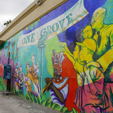 In this photo taken Saturday, July 6, 2013, a mural promoting the Bahamian heritage of the the Village West neighborhood of Coconut Grove in Miami, is shown on the outside wall of a grocery store. The community was settled by Bahamian immigrants in the 1880's, but has suffered from many years of decline and lack of investment. (AP Photo/Lynne Sladky)