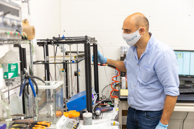 Emrah Celik, who developed a new additive manufacturing technique to produce a durable thermoset composite, checks on a 3D printer as it extrudes fiber-reinforced composite ink.