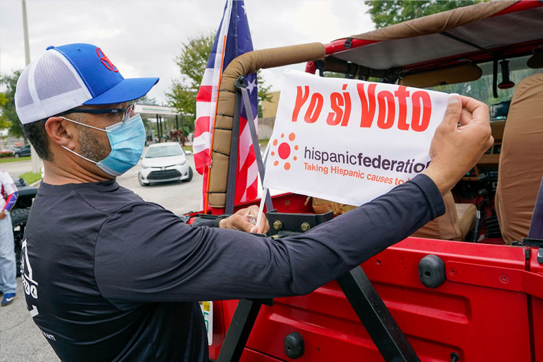 John Gimenez attaches a flag to his vehicle during an event hosted by the Hispanic Federation to encourage voting in the Latino community Sunday, Nov. 1, 2020, in Kissimmee, Fla. The Hispanic Federation is a non-partisan organization. (AP Photo/John Raoux)