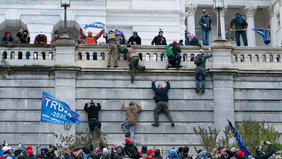 In this Wednesday, Jan. 6, 2021 file photo, supporters of President Donald Trump scale the west wall of the the U.S. Capitol in Washington. Associated Press