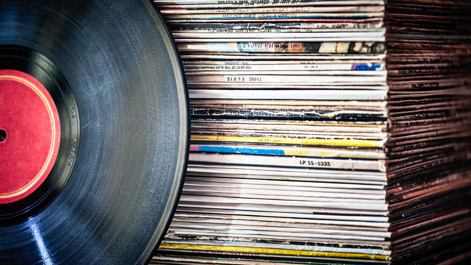 Vinyl record in front of a collection of albums