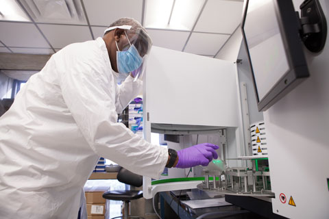Medical technologist Haider Saleh loads some COVID-19 samples into the a DNA extraction instrument used to detect the U.K. variant, at the Miller School of Medicine.