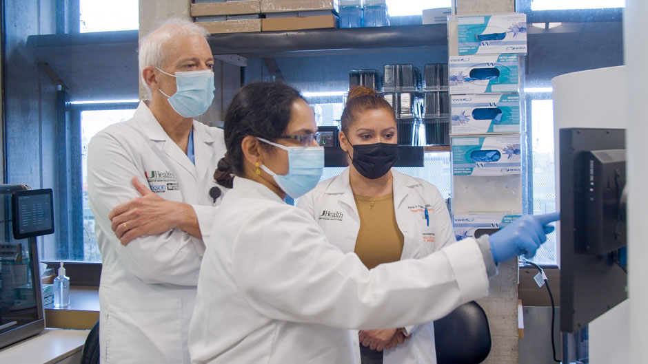 Dr. David Andrews, associate professor at the Miller School of Medicine, reviews data with senior medical technologist Ranjini Valiathan and Paola Pagan, executive director of laboratory operations.