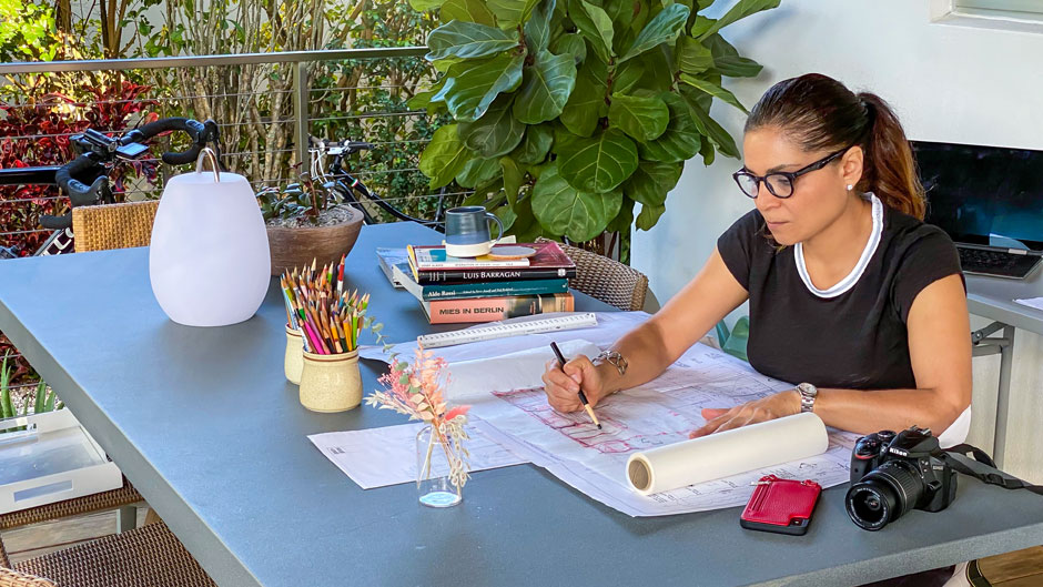 Carmen Guerrero works on architectural drawings in her backyard.