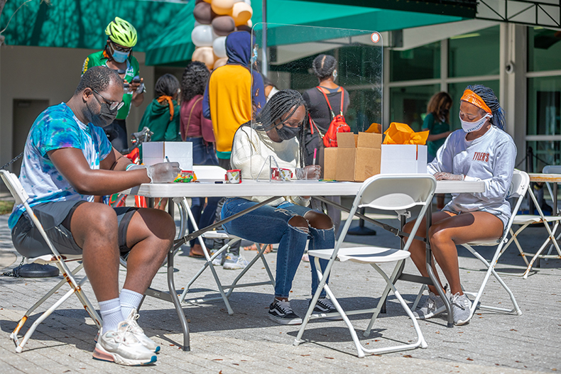 From left, sophomores Kristophe Smith-Walker, Samantha Ewiah and Sacha Braggs prepare care packages for frontline healthcare workers on Saturday as part of Social Justice Week's BAM Day of Service. Photo: Jenny Hudak/University of Miami