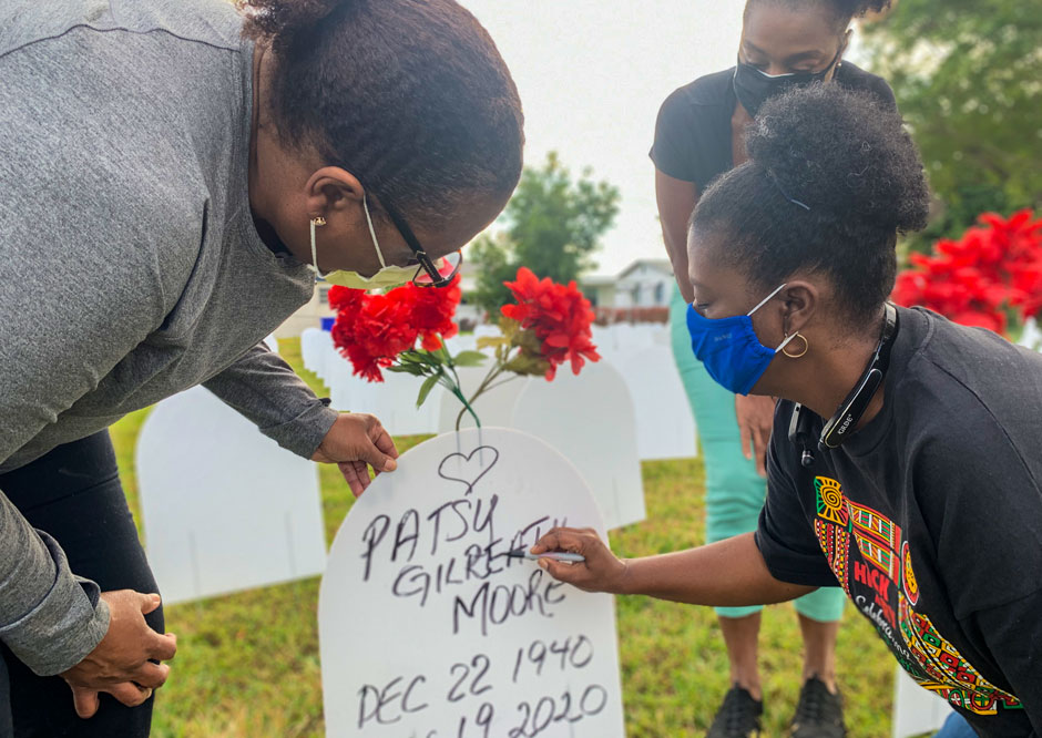 At Simonhoff Park in Liberty City, where a memorial honoring the many Miami-Dade County residents who have died of COVID-19 has been erected, Joanna Moore writes the name of her mother, Patsy Gilreath Moore, on one of the temporary tombstones while her sisters, Angela, left, and Rachel look on.     Photo credit: Robert C. Jones Jr.
