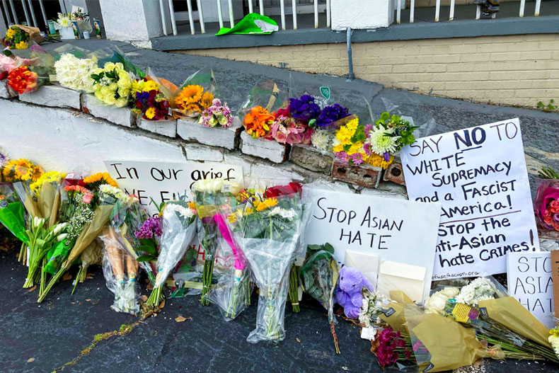 Flowers, candles and signs are displayed at a makeshift memorial on Friday, March 19, 2021, in Atlanta. Robert Aaron Long, a white man, is accused of killing several people, most of whom were of Asian descent, at massage parlors in the Atlanta area. (AP Photo/Candice Choi)