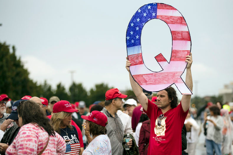 In this Aug. 2, 2018, file photo, a protesters holds a Q sign waits in line with others to enter a campaign rally with President Donald Trump in Wilkes-Barre, Pa. Facebook and Twitter promised to stop encouraging the growth of the baseless conspiracy theory QAnon, which fashions President Donald Trump as a secret warrior against a supposed child-trafficking ring run by celebrities and government officials. But the social media companies haven't succeeded at even that limited goal, a review by The Associated Press found. (AP Photo/Matt Rourke, File)