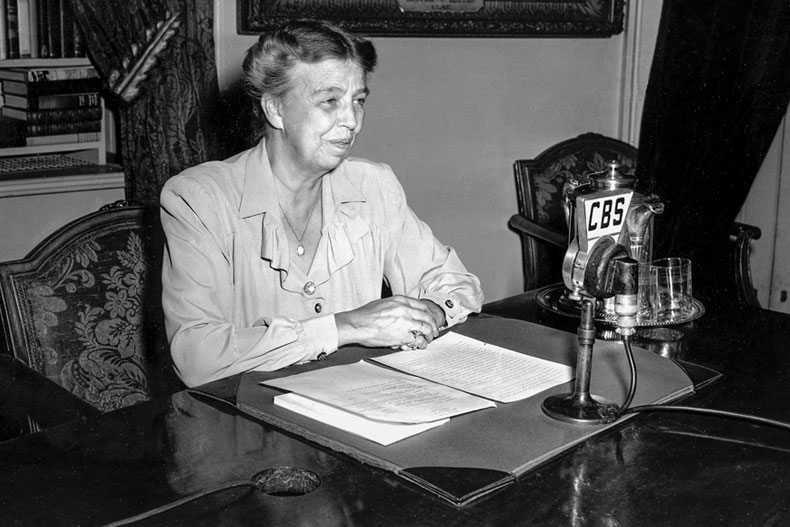 "First Lady Eleanor Roosevelt, celebrating her 60th birthday, broadcasts from the White House in Washington, D.C., on Oct. 11, 1944. The first lady is urging attendance at an exhibition of paintings by servicemen, ""The Army at War,"" which will tour the country as part of the upcoming war bond campaign. (AP Photo)"