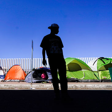 A migrant from Honduras seeking asylum in the United States stands in front of rows of tents at the border crossing, Monday, March 1, 2021, in Tijuana, Mexico. President Joe Biden is holding a virtual meeting with Mexican President Andrés Manuel López Obrador. Monday's meeting was a chance for them to discuss migration, among other issues. (AP Photo/Gregory Bull)