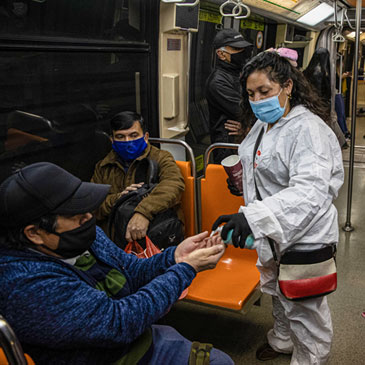 Denisse Leal dispenses alcohol gel to a commuter as she and her husband Mario Diaz ride a subway car in Santiago, Chile, Monday, Aug. 24, 2020. Leal and Diaz used to work as merchants in fairs all around Chile but the new coronavirus pandemic has left them with no way to earn a living, so now they disinfect subway cars in exchange for a tip. (AP Photo/Esteban Felix)