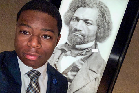 Douillon snapped a selfie with a portrait of Frederick Douglass.